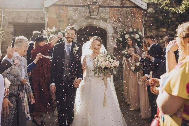 Couple walk through guests throwing confetti